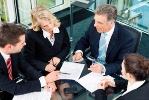 Un grupo de abogados discute los términos de un acuerdo de auto.