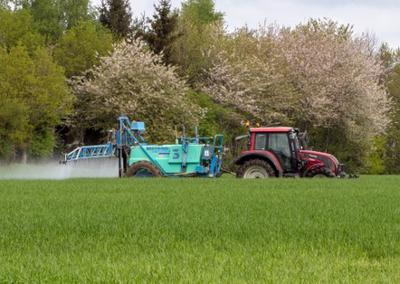 This image shows a farmer spraying his crops with Roundup