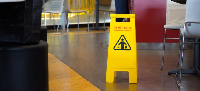 A wet floor sign in a building barring customers from entering the area.