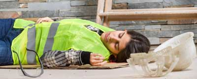 A woman lying on the ground injured at work